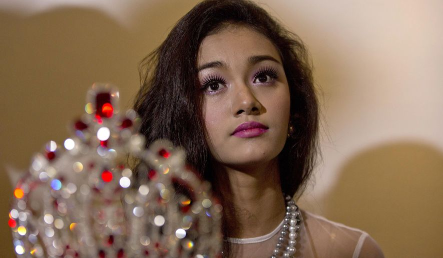 May Myat Noe, Myanmar's first international beauty queen, winner of the 2014 Miss Asia Pacific World, sits with her crown that she allegedly ran away with, during a press conference in Yangon, Myanmar Tuesday, Sept. 2, 2014. The dethroned beauty queen from Myanmar said she won't return her $100,000 worth crown until the pageant's organizers apologize for calling her a liar and a thief. (AP Photo/Gemunu Amarasinghe)