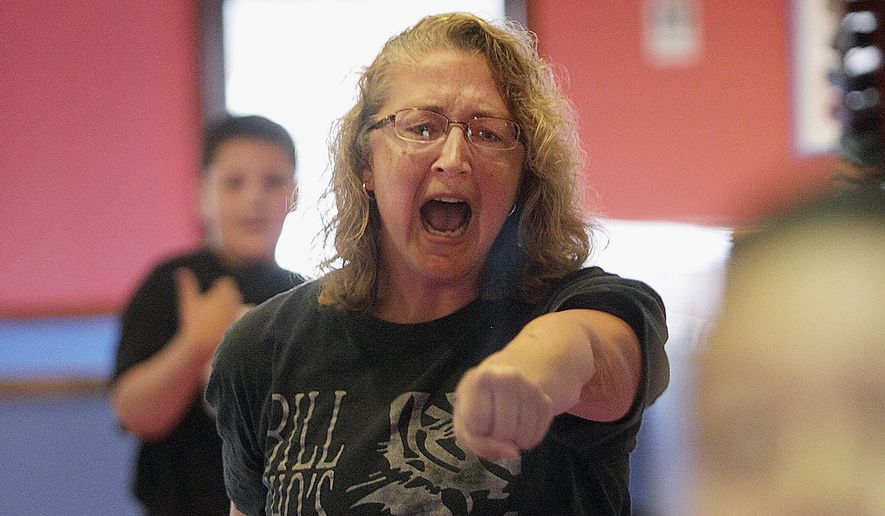 In this Aug. 12, 2014 photo, Dana Miller, of DeKalb, Ill., yells after a punch combination during a class at Bill Cho's United Taekwondo Center in Sycamore, Ill. Many women are taking classes at local fitness centers to learn about self-defense. Miller, 43, said her doctor was amazed by her flexibility. In a potentially dangerous situation with an attacker, she would be able to grab his arm, pull away and do some knee kicks. Miller says she feels more confident that she knows what she could do if I needed to. (AP Photo/Daily Chronicle, Danielle Guerra)  MANDATORY CREDIT