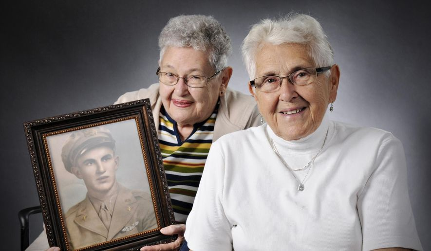 In this photo taken on Aug. 29, 2014, Mary Lou Stang, left, of Sartell, Minn., and her sister Margaret Thomas, of St. Cloud, Minn, pose for a photo with a portrait of their late brother Jerome Gross in St. Cloud. They are joining family members at a farm in France where the plane their brother Jerome was piloting crashed on Aug. 9, 1944. A monument is being erected by a local French organization to honor Gross and two other crew members for their wartime sacrifice.  (AP Photo/St. Cloud Times, Jason Wachter)