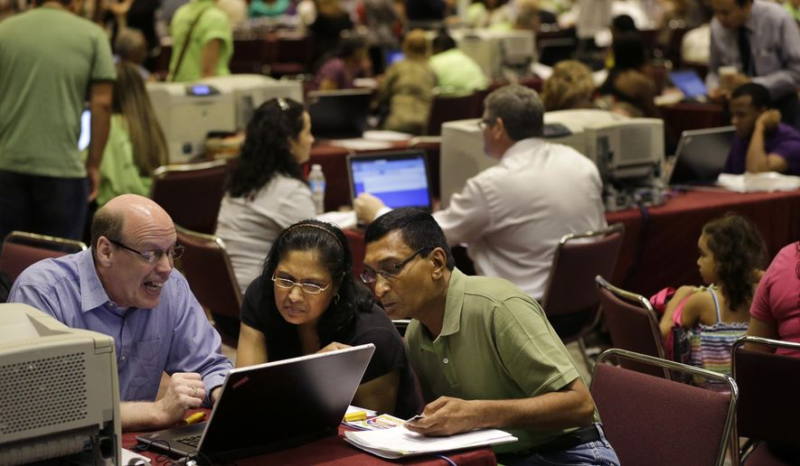 Former Revel Hotel Casino employees, Jignasha Shah, center, 45, and Ranjitsinh Rana, right, 56, get help from John McCaffery, as they file for unemployment benefits Wednesday, Sept. 3, 2014, in Atlantic City, N.J. (AP Photo/Mel Evans)