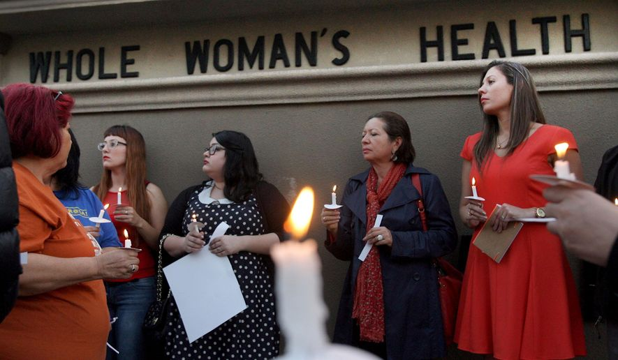 File - In this March 6, 2014 file photo, over 40 people hold a candle light vigil in front of the Whole Women's HealthClinic in McAllen, Texas. The clinic is reopening after a federal judge on Friday, Aug. 29, 2014, blocked part of sweeping new Texas abortion restrictions that also shuttered other facilities statewide six months ago. (AP Photo/ The Monitor, Delcia Lopez, File)