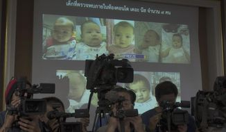 In this Tuesday, Aug. 12, 2014 file photo, Thai police display pictures of surrogate babies born to a Japanese man who is at the center of a surrogacy scandal during a press conference at the police headquarters in Chonburi, Thailand. A string of recent scandals has lifted a lid on Thailand's largely unregulated commercial surrogacy industry, which has been around for over a decade.  (AP Photo/Sakchai Lalit/File)