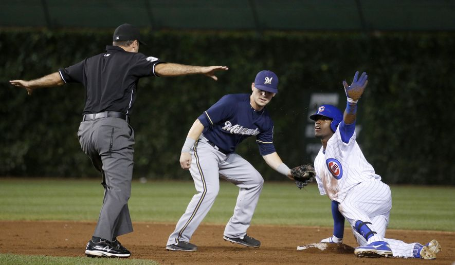 Chicago Cubs' Jorge Soler, right, asks for time from umpire Pat Hoberg, after sliding safely into second on a two-run double next to Milwaukee Brewers second baseman Scooter Gennetta during the third inning of a baseball game Wednesday, Sept. 3, 2014, in Chicago. (AP Photo/Charles Rex Arbogast)