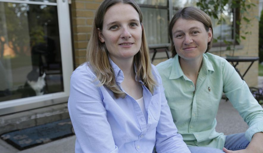 In this photo taken on Tuesday, Sept. 2, 2014, Barbara Webb, 33, left, poses for a photo with her wife Kristen Lasecki, 33, in Madison Heights, Mich. Webb, a former chemistry teacher at a suburban Detroit Catholic high school, said she was fired after becoming pregnant in a gay marriage. Although Webb's termination letter didn't give a reason for her firing, she said, her contract prohibits her from making lifestyle decisions or actions that are contrary to Catholic doctrine. (AP Photo/Detroit Free Press, Mandi Wright)  DETROIT NEWS OUT;  NO SALES, TV OUT, MANDATORY CREDIT