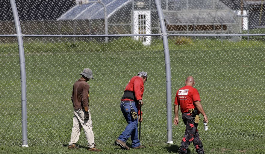 A crew checks for weak spots in the fence surrounding the Woodland Hills Youth Development Center Tuesday, Sept. 2, 2014, in Nashville, Tenn. According to a Department of Children's Services spokesman, more than 30 teenagers escaped from the facility Monday night by overwhelming 16 to 18 staff members, then crawling under a weak spot in the fence. (AP Photo/Mark Humphrey)