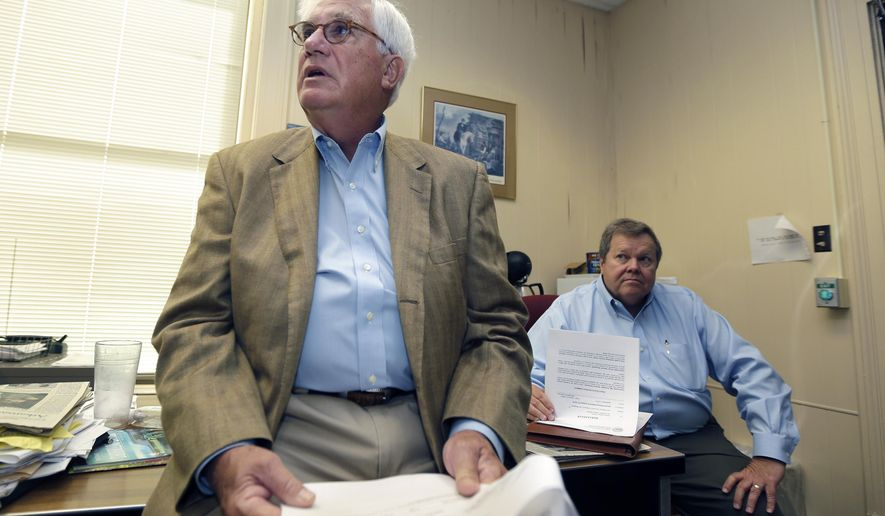 Arkansas Department of Finance and Administration Director Richard Weiss, left, is interviewed in the Press Room at the Arkansas state Capitol Wednesday, Sept. 3, 2014, in Little Rock, Ark., as Deputy Director Tim Leathers listens as they hold copies of the state revenue report. (AP Photo/Danny Johnston)