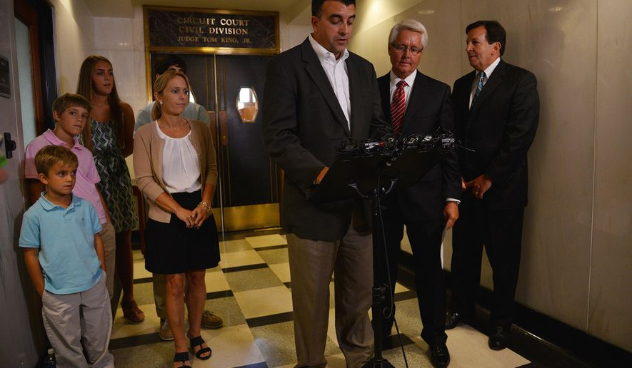 Ryan Bresette, center, of Overland Park, Kansas, reads a prepared statement at the Jefferson County Courthouse, Wednesday, Sept. 3, 2014, after his family reached a legal settlement with contractors who worked on a renovation project at the Birmingham-Shuttlesworth International Airport. Bresette's son, Luke,10,  died on March 22, 2013, when a multi-user flight information display fell on him and several of his family members. The terms of the settlement remain confidential. (AP Photo/AL.com, Tamika Moore) MAGS OUT