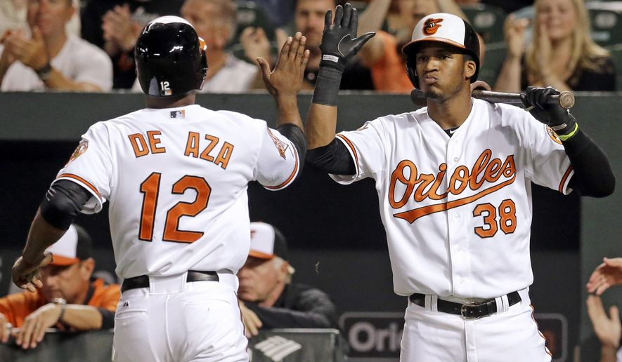 Baltimore Orioles' Jimmy Paredes, right, greets teammate Alejandro De Aza after he scored on a single by Chris Davis in the first inning of an interleague baseball game against the Cincinnati Reds, Tuesday, Sept. 2, 2014, in Baltimore. (AP Photo/Patrick Semansky)