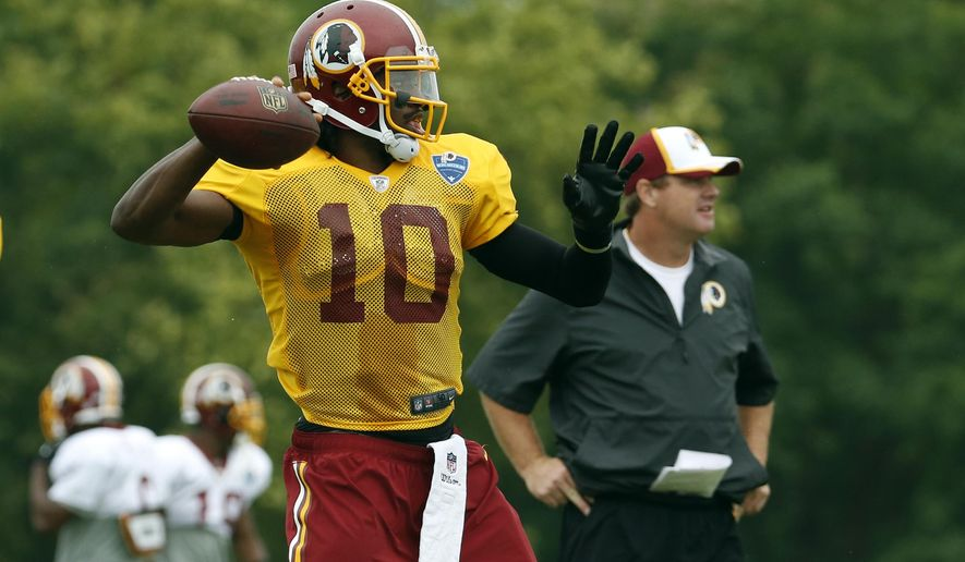 FILE - In this July 27, 2014, file photo, Washington Redskins head coach Jay Gruden, right, stands as quarterback Robert Griffin III prepares to throw during practice at the team's NFL football training facility in Roanoke, Va. It's the third time around for Robert Griffin III as he prepares to lead the Washington Redskins into their regular season opener.(AP Photo/Alex Brandon, File)