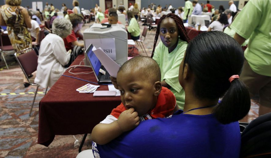 Former Revel Hotel Casino employees, Fatuma Kamara holds her 11-month-old baby Mussa as she gets help from Kristanna Brown as she files for unemployment benefits Wednesday, Sept. 3, 2014, in Atlantic City, N.J. (AP Photo/Mel Evans) **FILE**