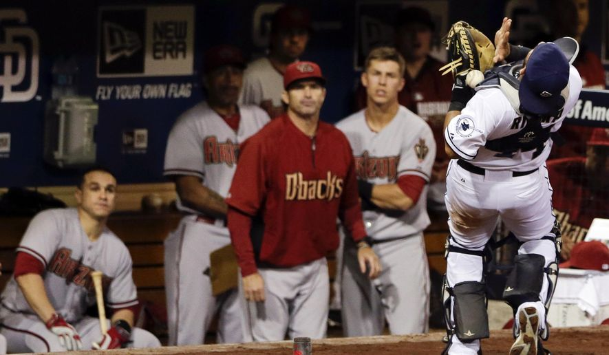 San Diego Padres catcher Rene Rivera, right, drops a foul ball hit by the Arizona Diamondbacks' David Peralta in front of the Diamondbacks dugout during the fourth inning of a baseball game Tuesday, Sept. 2, 2014, in San Diego. (AP Photo/Gregory Bull)