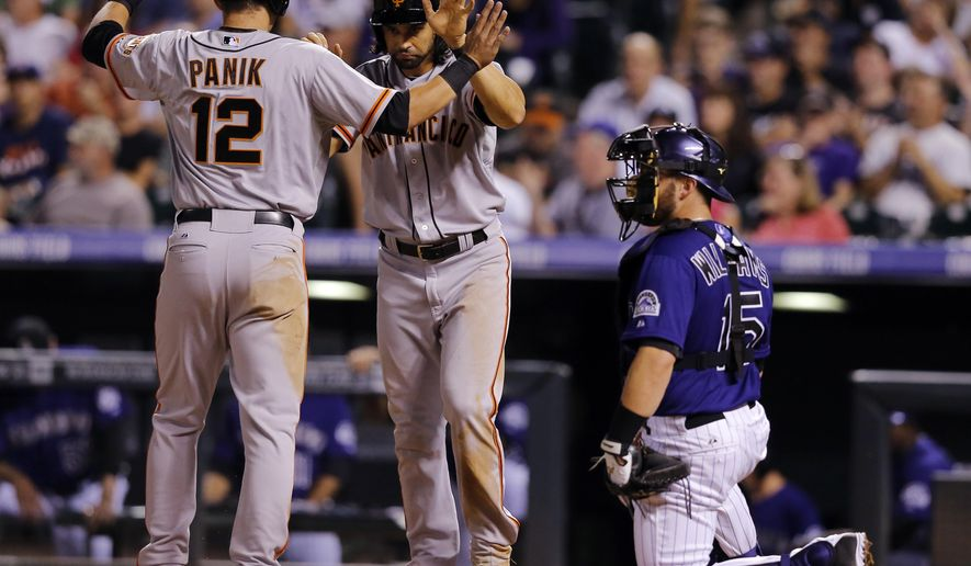 San Francisco Giants' Joe Panik (12) and Angel Pagan celebrate scoring on a Buster Posey two RBI double against the Colorado Rockies during the seventh inning of a baseball game Tuesday, Sept. 2, 2014, in Denver. (AP Photo/Jack Dempsey)