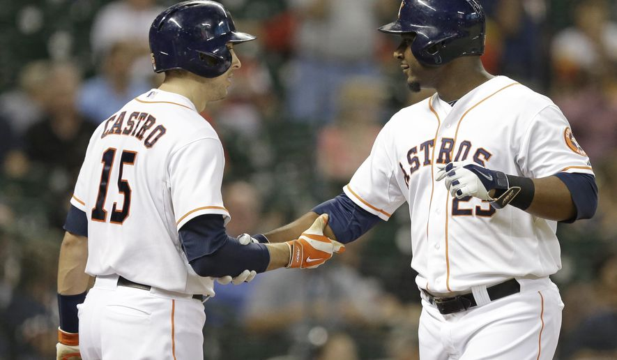 Houston Astros' Chris Carter (23) is welcomed back to home by Jason Castro (15) after hitting a solo home run against the Los Angeles Angels in the second inning of a baseball game Wednesday, Sept. 3, 2014, in Houston. (AP Photo/Pat Sullivan)