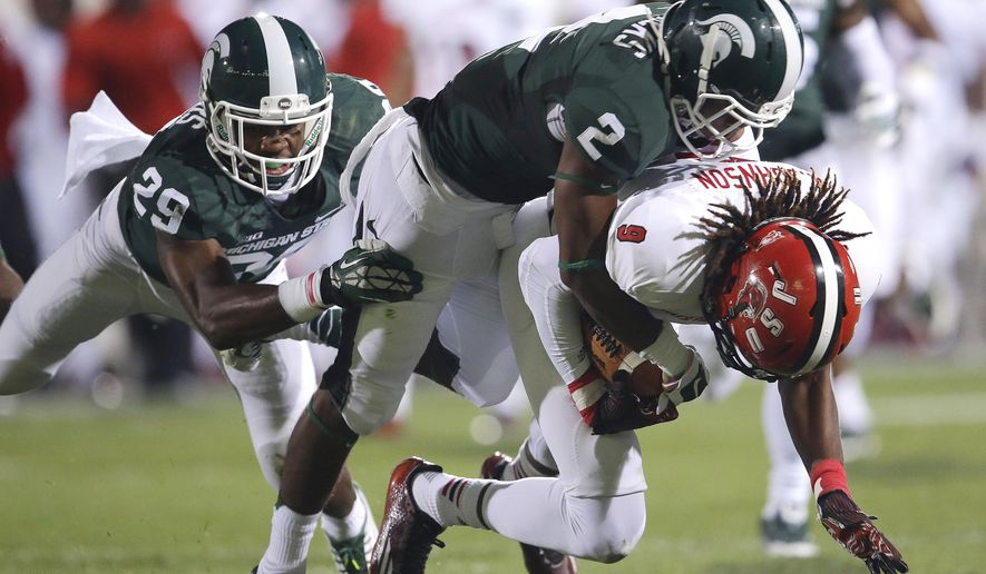 FILE - In this Aug. 29, 2014, file photo, Jacksonville State wide receiver Anthony Johnson (9) is brought down by Michigan State cornerback Darian Hicks (2) and safety Mark Meyers (29) in the second half of an NCAA college football game in East Lansing, Mich. Big Ten defending champions Michigan State play at No. 3 Oregon on Saturday, Sept. 6, 2014.  (AP Photo/Paul Sancya, File)