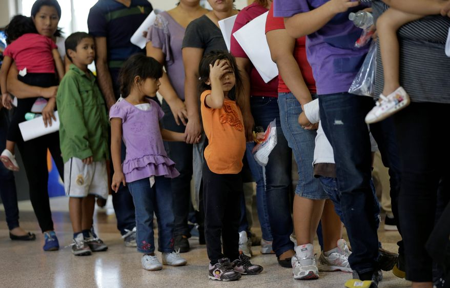 In this June 20, 2014, file photo, immigrants who entered the U.S. illegally stand in line for tickets at the bus station after they were released from a U.S. Customs and Border Protection processing facility in McAllen, Texas. The immigrants entered the country through an area referred to as zone nine. (AP Photo/Eric Gay) ** FILE **