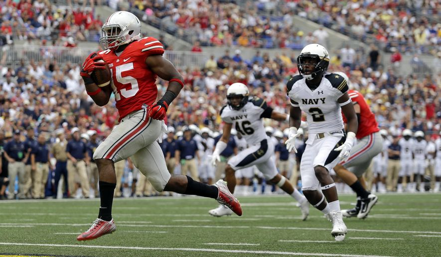 FILE - In this Aug. 30, 2014, file photo, Ohio State running back Ezekiel Elliott, left, runs past Navy safety Parrish Gaines (2) and linebacker Chris Johnson (46) for a touchdown in the second half of an NCAA college football game in Baltimore. After a 34-17 victory over Navy in the opener, coach Urban Meyer is pleased with the job done by Elliott, who gained 44 yards on 12 carries including this 10-yard touchdown run. (AP Photo/Patrick Semansky, File)