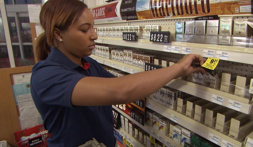 This undated photo provided by CVS Health, a CVS store employee removes tobacco products from the store shelves in East Greenwich, R.I.  (AP Photo/CVS Health)