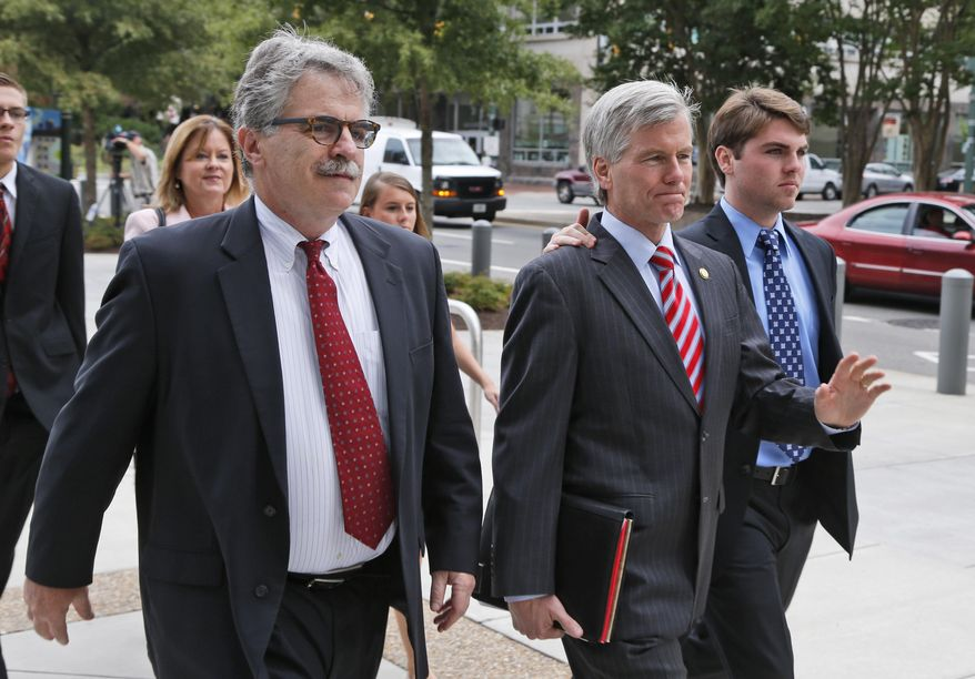 Former Virginia Gov. Bob McDonnell, center, arrives at federal court with his son Bobby, right and attorney Daniel Small, left,  for the second day of jury deliberations in his corruption trial in Richmond, Va., Wednesday, Sept. 3, 2014.    (AP Photo/Steve Helber)