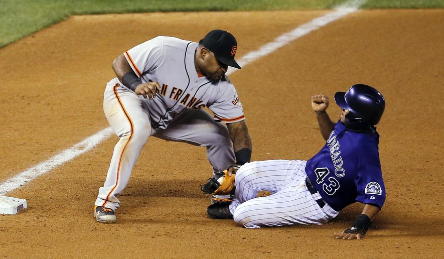 San Francisco Giants third baseman Pablo Sandoval tags out Colorado Rockies second baseman Rafael Ynoa at third during the seventh inning of a baseball game Tuesday, Sept. 2, 2014, in Denver. (AP Photo/Jack Dempsey)