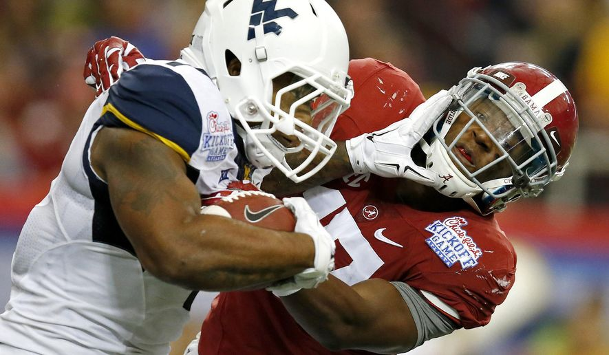 West Virginia's Rushel Shell (7) tries to fight off Alabama's Kenyan Drake (17) on a punt return during the second half of an NCAA college football game Saturday, Aug. 30, 2014, in Atlanta. (AP Photo/Brynn Anderson)