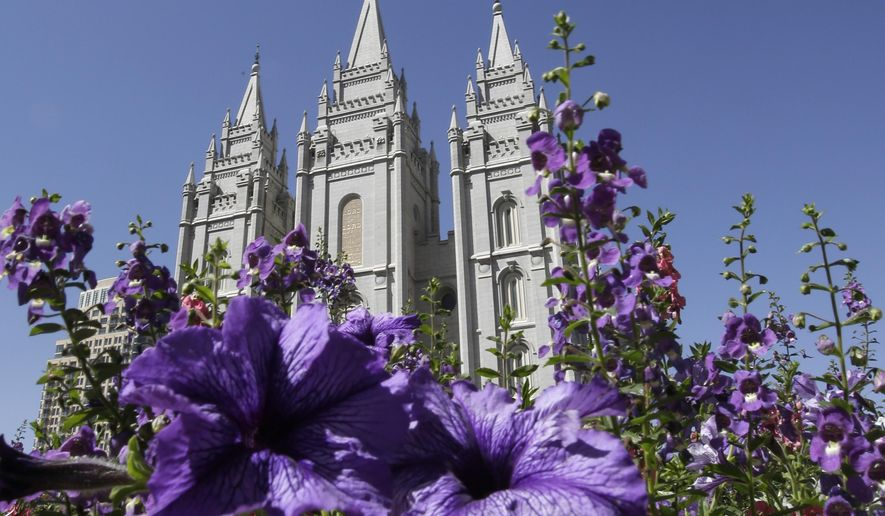 """Flowers bloom in front of the Salt Lake Temple in Temple Square in Salt Lake City on Wednesday, Sept. 3, 2014. The Church of Jesus Christ of Latter-day Saints on Wednesday unveiled a new collection that features some of the faith's most treasured artifacts, including a page from the original Book of Mormon manuscript written by founder Joseph Smith. The """"Foundations of Faith"""" exhibit that opens to the public this week in the church's history library in Salt Lake City. (AP Photo/Rick Bowmer)"""