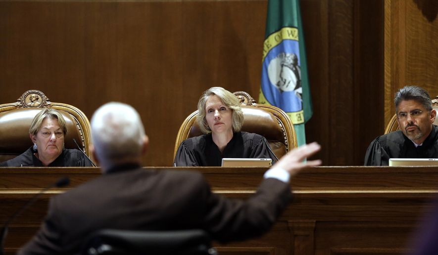 Supreme Court Justices Susan Owens, left, Debra Stephens, center, and Steven Gonzalez listen to Thomas Ahearne, attorney for the coalition that sued the state over education funding, during a hearing before the state Supreme Court Wednesday, Sept. 3, 2014, in Olympia, Wash. The court ordered lawmakers to explain why they haven't followed its 2012 decision to fix the way Washington pays for public education. Lawmakers, the governor and others say the court needs to be patient and give the Legislature more time to fulfill the orders from the 2012 McCleary decision. (AP Photo/Elaine Thompson)