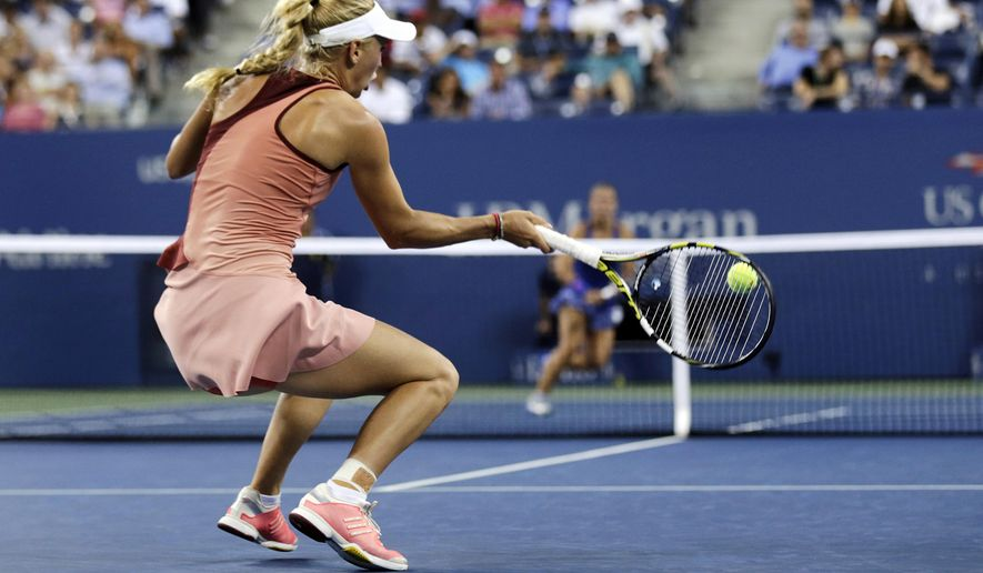 Caroline Wozniacki, of Denmark, returns to Sara Errani, of Italy, during the quarterfinal round of the 2014 U.S. Open tennis tournament, Tuesday, Sept. 2, 2014, in New York. Wozniacki defeated Errani 6-0, 6-1. (AP Photo/Charles Krupa)