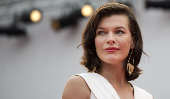 Actress Milla Jovovich poses for photographers as she arrives for the screening of Cymbeline at the 71st edition of the Venice Film Festival in Venice, Italy, Wednesday, Sept. 3, 2014. (AP Photo/David Azia)
