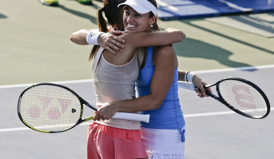 Martina Hingis, right, hugs Flavia Pennetta after the two defeated Cara Black and Sania Mirza in a semifinal doubles match of the 2014 U.S. Open tennis tournament, Thursday, Sept. 4, 2014, in New York. (AP Photo/Charles Krupa)
