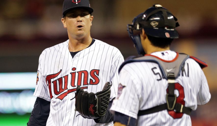 Minnesota Twins pitcher Kyle Gibson, left, and catcher Kurt Suzuki confer in the fourth inning of a baseball game against the Los Angeles Angels, Thursday, Sept. 4, 2014, in Minneapolis. Gibson gave up four runs in the fourth. (AP Photo/Jim Mone)