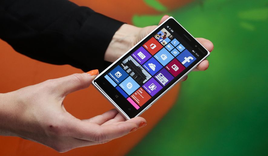 A woman shows the new Lumia 830 smart phone during a Microsoft Nokia presentation event at the consumer electronic fair IFA in Berlin, Thursday, Sept. 4, 2014. (AP Photo/Markus Schreiber)