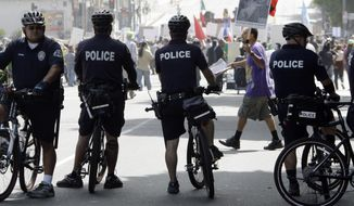 FILE - In this Sept. 18, 2010 file photo, officers on bicycles keep watch as demonstrators protesting several incidents of alleged Los Angeles Police Department brutality, including the fatal shooting of Manuel Jamines a month ago, stand outside the LAPD's Rampart Station in the Westlake district of Los Angeles. Police departments across the U.S. are using technology to try to identify problem officers before their misbehavior harms innocent people, embarrasses their employer, or invites a costly lawsuit,  from citizens or the federal government.  The Los Angeles Police Department agreed to set up their $33 million early warning systems after the so-called Rampart scandal in which an elite anti-gang unit was found to have beaten and framed suspected gang members. The system was then implemented in 2007. (AP Photo/Reed Saxon)