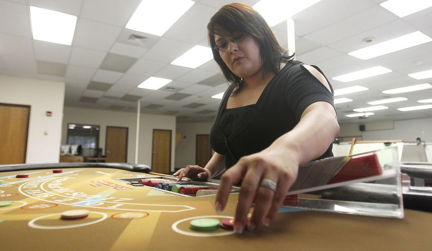 ADVANCE FOR USE SATURDAY, SEPT. 6 - In this photo taken on Aug. 29, 2014, Adriana Pineda pays out chips during her blackjack dealers class taught by Cactus Petes Casino at the College of Southern Idaho in Twin Falls, Idaho. (AP Photo/The Times-News, Drew Nash) MANDATORY CREDIT