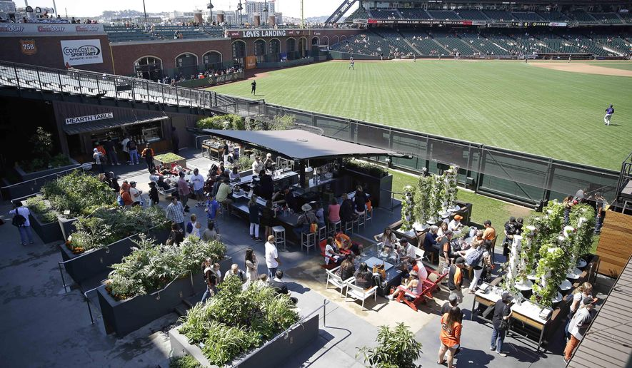 In this photo taken Thursday, Aug. 28, 2014, people visit the Edible Garden located in center field at AT&T Park before the San Francisco Giants' baseball game in San Francisco. From the 20 some cutting-edge, space-saving vertical towers that require far less soil and water to the more traditional raised beds and planter boxes, the garden is not only a tranquil spot in the middle of a bustling ballpark along San Francisco Bay but also an outdoor classroom to teach children and teens even adults for that matter about healthy eating from fresh ingredients and urban farming. (AP Photo/Eric Risberg)