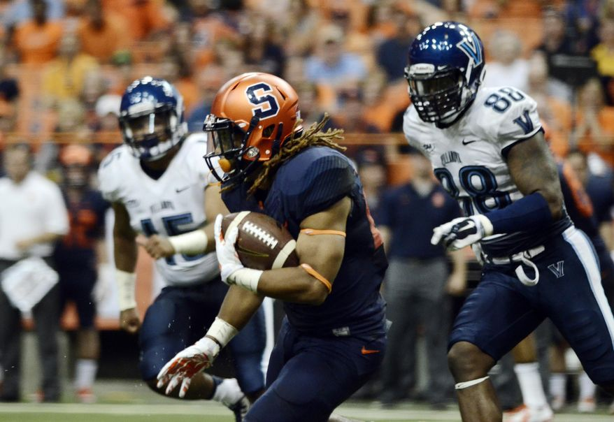 Syracuse's Prince-Tyson Gulley, center, charges past the Villanova defense during their game at the Carrier Dome in Syracuse, N.Y., Friday, Aug. 29, 2014. Syracuse defeated Villanova, 27-26, in overtime. (AP Photo/Heather Ainsworth)