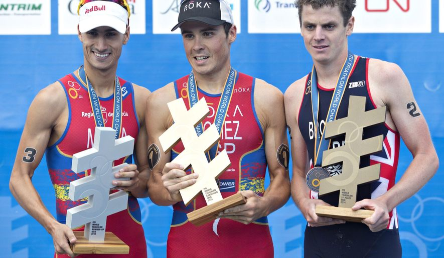 Mario Mola of Spain (3), Javier Gomez Noya of Spain (1) and Jonathan Brownlee (2) hold their trophies during the medal ceremonies at the Elite Men Championship at the ITU World Triathlon Grand Final in Edmonton, Alberta, on Sunday Aug. 31, 2014.  (AP Photo/The Canadian Press, Jason Franson)