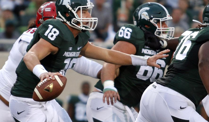 FILE - In this Aug. 29, 2014, file photo, Michigan State quarterback Connor Cook (18) scrambles against Jacksonville State during the first quarter of an NCAA college football game  in East Lansing, Mich. When No. 7 Michigan State plays at No. 3 Oregon on Saturday, the team with the old-school offense will be the unusual one. While it's become more difficult to categorize offenses these days as philosophies and schemes are blended and combined, the Spartans are among a dwindling number of teams still using what can best be described as a traditional, prostyle attack, featuring tight ends, fullbacks and the quarterback regularly taking a snap from under center. (AP Photo/Al Goldis, File)