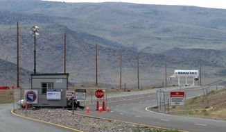 FILE - This Aug. 1, 2014 file photo shows security guards at the gate to the site Tahoe Reno Industrial Center about 15 miles east of Reno, Nevada. Tesla Motors has selected the site in Nevada for a massive, $5 billion factory that it will build to pump out batteries for a new generation of electric cars, a person familiar with the company's plans said Wednesday, Sept. 3, 2014. (AP Photo/Scott Sonner, File)