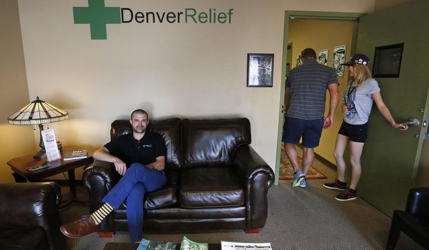 In this Aug. 25, 2014 photo, Kayvan Khalatbari, left, sits on the couch in the lobby of his medical and recreational marijuana store Denver Relief, as his employee Allison Woods escorts a customer into the shop, in Denver. Khalatbari also runs Denver Relief Consulting, which assists current and would-be marijuana-related businesses around the country, as well as owning a chain of pizza restaurants in Denver. (AP Photo/Brennan Linsley)