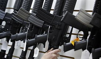 An Arizona made AR-15 is pulled from the display at Caswells Shooting Range Tuesday, April 6, 2010, in Mesa, Ariz. (AP Photo/Matt York) ** FILE **