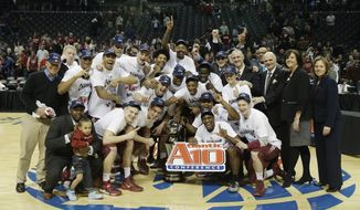 Saint Joseph's players, along with supporters and officials, pose with the championship trophy after an NCAA college basketball game against VCU in the championship round of the Atlantic 10 Conference tournament at the Barclays Center in New York, Sunday, March 16, 2014. St. Joseph's defeated VCU 65-61. (AP Photo/Seth Wenig)