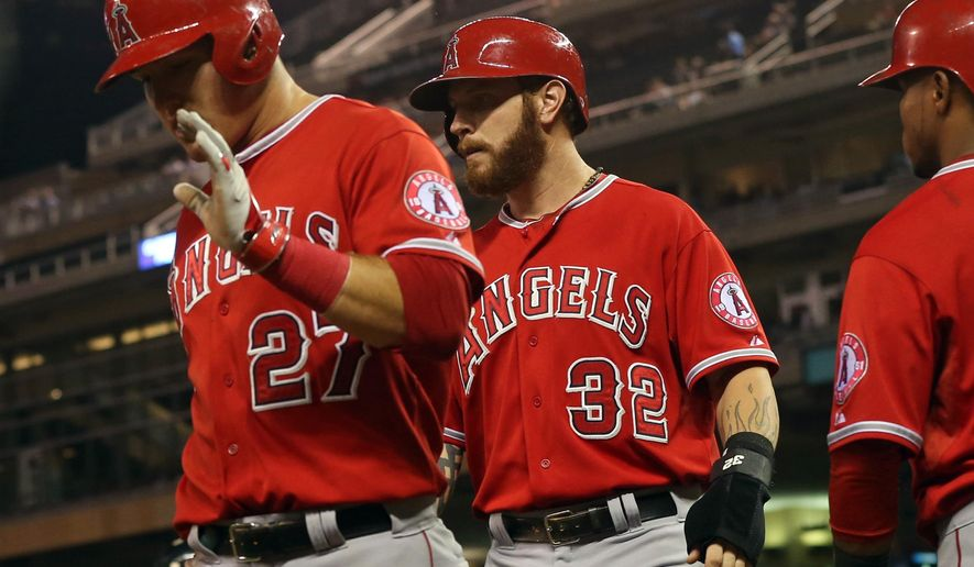 Los Angeles Angels' Mike Trout, left, and Josh Hamilton, center, head to the dugout after scoring on a double by Howie Kendrick off Minnesota Twins pitcher Kyle Gibson in the fourth inning of a baseball game, Thursday, Sept. 4, 2014, in Minneapolis. (AP Photo/Jim Mone)