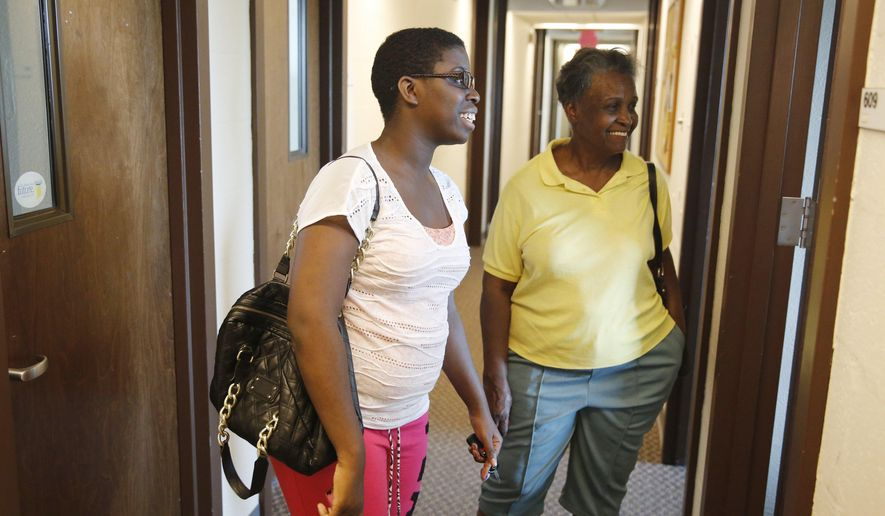 ADVANCE FOR SATURDAY, SEPT. 6 - In this photo taken on Aug. 29, 2014, 21st Century Scholar Precious McMillon, left, shows her grandmother Alma McMillon around the office on the Indiana University campus in Bloomington, Ind.  The 21st Century Scholar program has grown by 90 percent at IU in the past seven years. And for the first time this year, IU plans to be a part of recruiting scholars.   (AP Photo/Bloomington Herald-Times, David Snodgress)