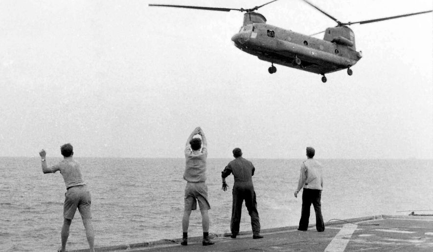 "In this April 29, 1975 photo provided by courtesy of American Experience and Hugh Doyle, aboard the USS  Kirk, crew members signal the Chinook to hover over the deck and drop its passengers out.  The new documentary film, ""Last  Days in Vietnam,"" directed and produced by Rory Kennedy, recounts the dramatic events surrounding the 1975 military evacuation of Saigon during the Vietnam War. The film releases on Friday, Sept. 5, 2014. (AP Photo/Courtesy American Experience, Courtesy Hugh Doyle)"