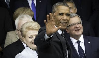 U.S. President Barack Obama, center, waves as he arrives for a group photo during a NATO summit at the Celtic Manor Resort in Newport, Wales on Thursday, Sept. 4, 2014. In a two-day meeting leaders will discuss, among other issues, the situation in Ukraine and Afghanistan. (AP Photo/Jon Super)
