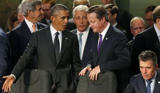 President Barack Obama speaks with British Prime Minister David Cameron as NATO leaders meet regarding Afghanistan at the NATO summit at Celtic Manor in Newport, Wales, Thursday, Sept. 4, 2014. From left are, Secretary of State John Kerry, the president, Defense Secretary Chuck Hagel and NATO Secretary-General Anders Fogh Rasmussen. (AP Photo/Charles Dharapak)