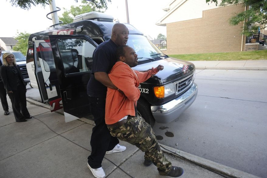FILE - In this July 30, 2014 file photo Jamre Pearson is held back by a friend outside his home after his 8-year-old son, Jakari, was shot while sleeping inside the family's Detroit home. A preliminary hearing to determine if the case goes to trial is scheduled for Thursday, Sept. 4, 2014 for 28-year-old Calvin Mosby and 17-year-old Devaunte Starks who are charged with first-degree murder in Jakari's death. (AP Photo/Detroit News, David Coates, File)