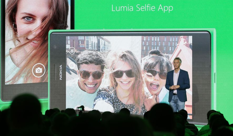 Chris Weber, CVP, Mobile Devices Sales of Microsoft,   presents the new Lumia Selfie App for their smart phones during his keynote speech  during  a Microsoft Nokia presentation event at the consumer electronic fair IFA in Berlin, Thursday, Sept. 4, 2014. (AP Photo/Markus Schreiber)