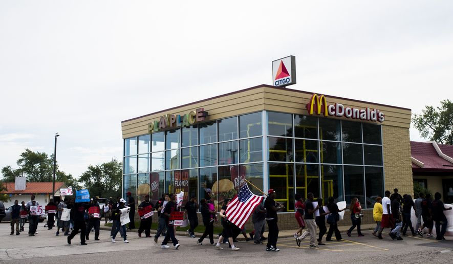 About 150 protestors gather to have the minimum wage raised to $15 an hour, in front of McDonald's on Stewart Avenue near Dort Highway on Thursday, Sept. 4, 2014 in Flint, Mich. Flint Police took into custody 25 protesters, who sat across the street to not allow traffic to pass in front of the fast food establishment. (AP Photo/The Flint Journal, Jake May)
