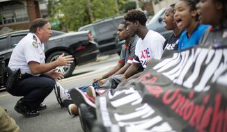 Atlanta Police Deputy Chief Joe Spillane talks with protestors before they are arrested for blocking the street  outside a McDonald's restaurant on Thursday. (AP Photo/David Goldman)